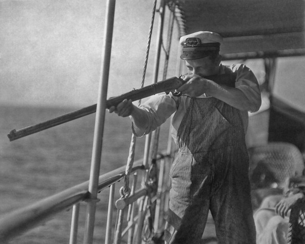 Fishing boat captain Jake Martin aims his rifle at a shark, circa 1925. Martin maintains that the presence of sharks interferes with good fishing. (Photo by Keystone View Company/FPG/Archive Photos/Getty Images)