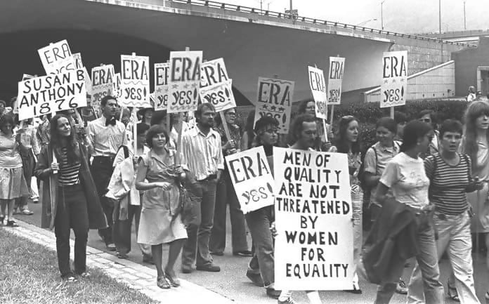 Macintosh HD:Users:brittanyloeffler:Downloads:Upwork:Women's Rights:crowd-marching-for-era-rally-90196004-58d66f3c5f9b58468348ee02-696x433.jpg